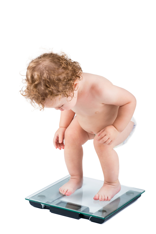 © Famveldman | Dreamstime.com - Very Funny Baby Watching Her Weight, Isolated Photo
